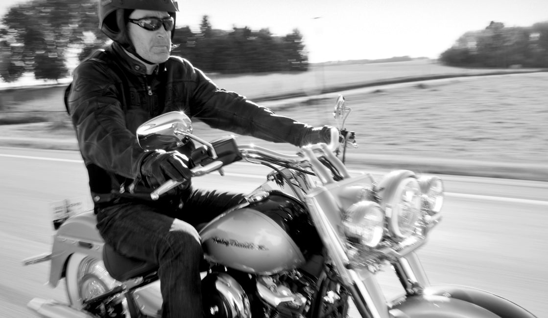 Ken Schmidt wearing a helmet and sunglasses, riding a Harley-Davidson motorcycle